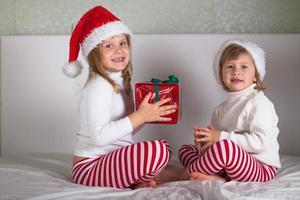 lustige Kinder in ihren Pyjamas und Weihnachtsmützen auf dem Bett