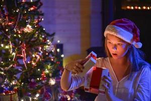 Weihnachtszeit, ein ausdrucksstarkes junges Mädchen, das ihre Geschenkbox öffnet