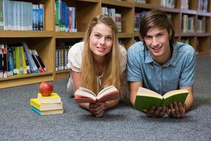 Studenten lesen Buch auf dem Boden der Bibliothek liegend foto