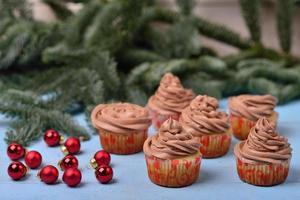 Cupcakes mit Schokoladencreme auf einem blauen hölzernen Hintergrund