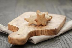 hausgemachte sternförmige Ingwerplätzchen auf Olivenbrett