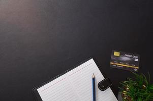 Rekordbuch, Bleistift und Kreditkarte auf dem Schreibtisch
