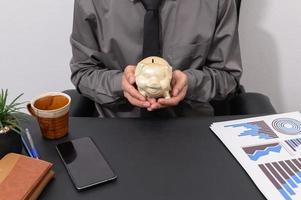 Geschäftsmann hält Sparschwein an seinem Schreibtisch foto