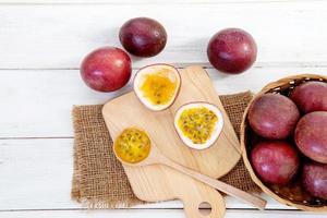 Schließen Sie eine frische Passionsfrucht auf weißem Holztischhintergrund foto