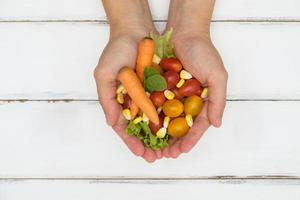 Person, die Gemüse auf weißem hölzernem Hintergrund hält