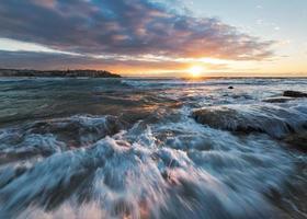 Sonnenaufgang am Strand mit rauschendem Wasser foto