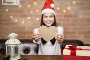 junge lächelnde Frau, die roten Weihnachtsmannhut trägt, der ein Herz zeigt