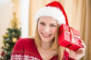festliche Blondine hält ein Geschenk