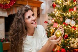 Porträt der lächelnden jungen Frau, die den Weihnachtsbaum verziert