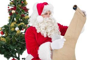 Santa mit Brille liest ein Pergament foto