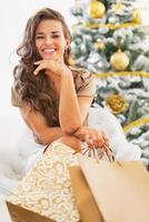 junge Frau mit Einkaufstüten, die nahe Weihnachtsbaum sitzen foto