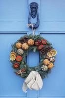 hausgemachter Weihnachtskranz, der an der blauen Tür hängt