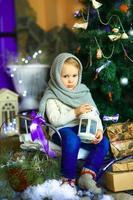 das Mädchen in der Nähe eines Weihnachtstannenbaums
