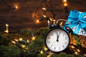 Weihnachtsbaum, Geschenke, Lichter und Uhr über der Holzwand foto