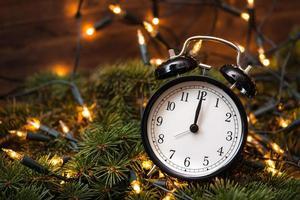 Weihnachtsbaum, Lichter und Uhr über der Holzwand foto