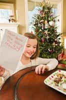 glückliches Kind, das Kekse und Weihnachtswunschliste zum Weihnachtsmann anbietet