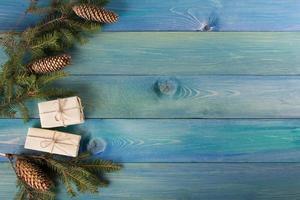 Weihnachtstannenbaum mit Dekoration auf blauem Holzbrett.