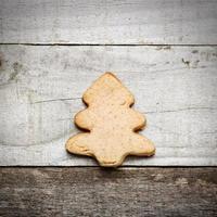 hausgemachter Keks in Weihnachtsbaumform auf hölzernem Hintergrund