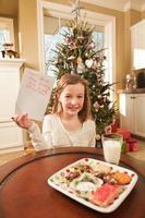 Kind, das Kekse anbietet und Weihnachtswunschliste zu Santa schreibt