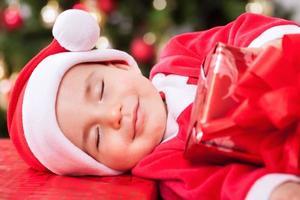 lächelndes Babykind Weihnachtsmann mit schönen Träumen
