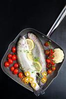 roher Fisch mit Gemüse in der Pfanne