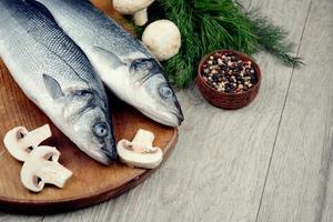 roher Seebarschfisch auf dem Holzbrett foto