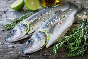 zwei rohe Seebarsche mit Limette und Rosmarin foto