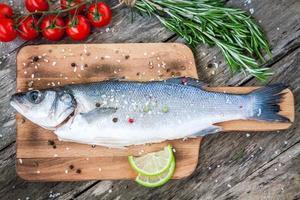 zwei rohe Seebarsche mit Limette, Kirschtomaten und Rosmarin foto