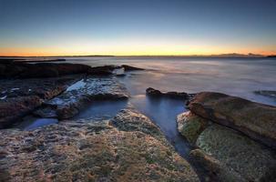 Morgendämmerungsküste auf den Felsen bei Cronulla, Australien foto