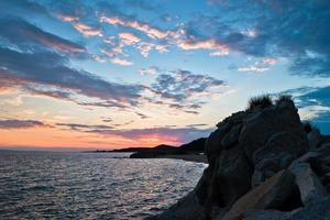 Silhouette von Seefelsen und Reflexion der Wolkenlandschaft bei Sonnenuntergang