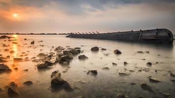 sinkendes Boot auf dem Sonnenuntergang foto