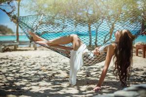 junge schöne Frau, die in der Hängematte auf dem Meer genießt