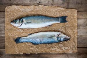 zwei rohe Seebarschfische auf hölzernem Hintergrund foto