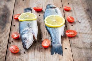 zwei rohe Seebarschfische mit Zitronen- und Kirschtomaten foto
