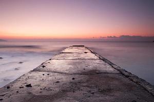 Sonnenaufgang am felsigen Ufer des Schwarzen Meeres mit altem Pier