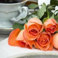 Tasse Kaffee und ein Strauß Rosen foto