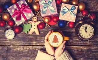 Frau, die Tasse Kaffee nahe Weihnachtsgeschenken hält