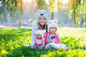 Mutter und Tochter spielen im Park mit einer Puppe