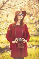 Frauen mit Kamera im Blütenapfelbaumgarten foto