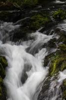 Kaskade von kleinen Wasserfällen über moosigen Felsen, Langzeitbelichtung.