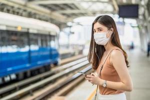 junge asiatische Passagierin, die eine chirurgische Maske trägt und Musik über ein intelligentes Mobiltelefon im U-Bahn-Zug hört, wenn sie in der Großstadt bei Covid19-Ausbruch, Infektion und Pandemiekonzept reist foto