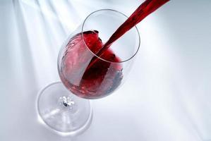 Rotwein in ein Glas gießen foto