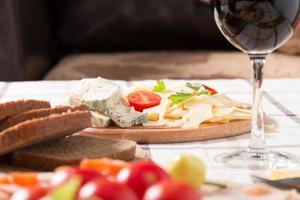 hausgemachtes Abendessen mit Brot, Tomaten, Käse, Schinken und Wein
