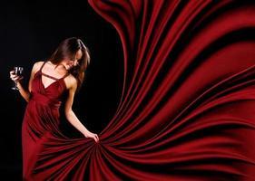 Wein haltende Dame mit weinfarbenem fließendem Kleid foto