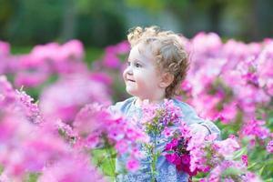 schönes lockiges Baby, das im Garten unter rosa Blumen spielt