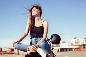 Biker Mädchen sitzt auf Vintage Custom Motorrad
