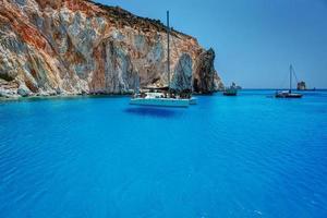 transparentes Wasser mit bunten Felsen und Segelbooten