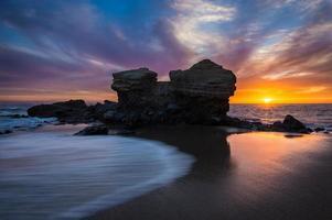 bunte Sonnenuntergangsseelandschaft mit dramatischem Felsen und Sunburst