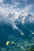 gelber Gleitschirm über alpgrünem Tal
