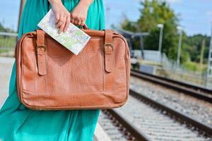 Frauenhände halten eine Karte und einen Koffer am Bahnhof